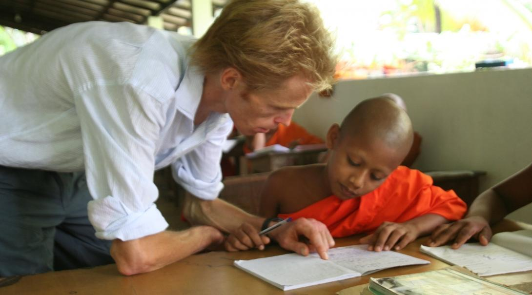 A young monk receives help from a volunteer teaching English in Sri Lanka